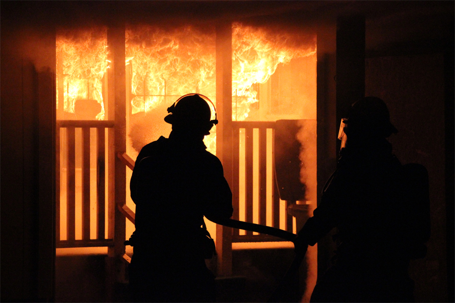 Fire fighter putting out a first floor house fire