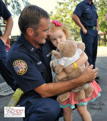Fire fighter holding child while she holds a teddy bear