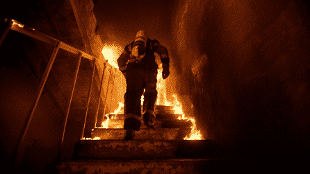 Fire fighter walking up a flight of stairs that are on fire