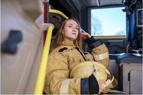 Female fire fighter sitting in the back of a fire truck deep in thought