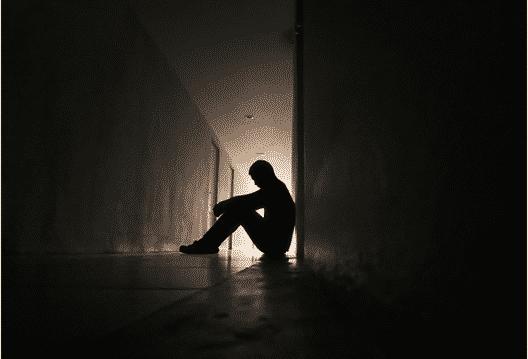 Depressed fire fighter sitting on the ground in a dark outdoor hallway