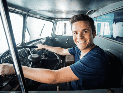 Fire fighter smiling with his hands on the wheel of a fire truck