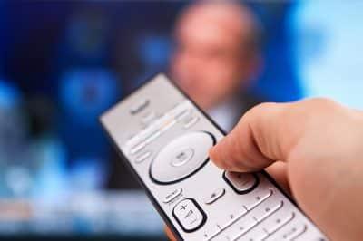 Hand holding remote flipping through coronavirus news