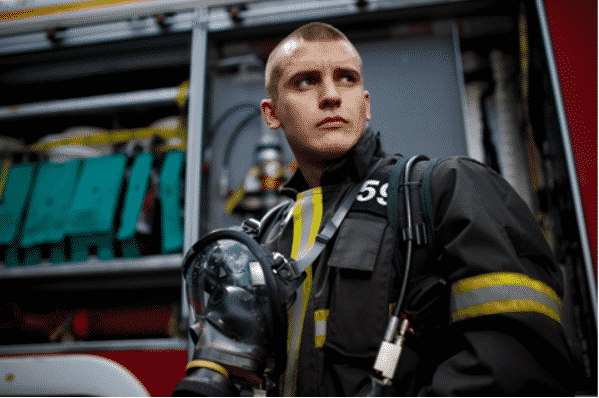 Fire fighter looking to the right in uniform standing in front of a fire truck