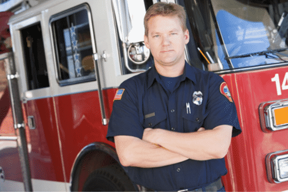 Firefighter in blue uniform standing in front of a fire truck