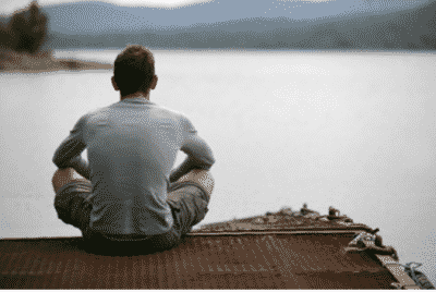 Man in recovery sitting on a dock looking at a lake