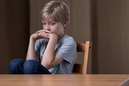 kid sitting at table depressed after bad news