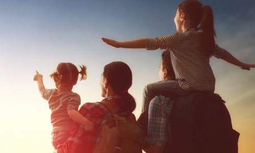A family looks out at the sunset with hope for a new day.